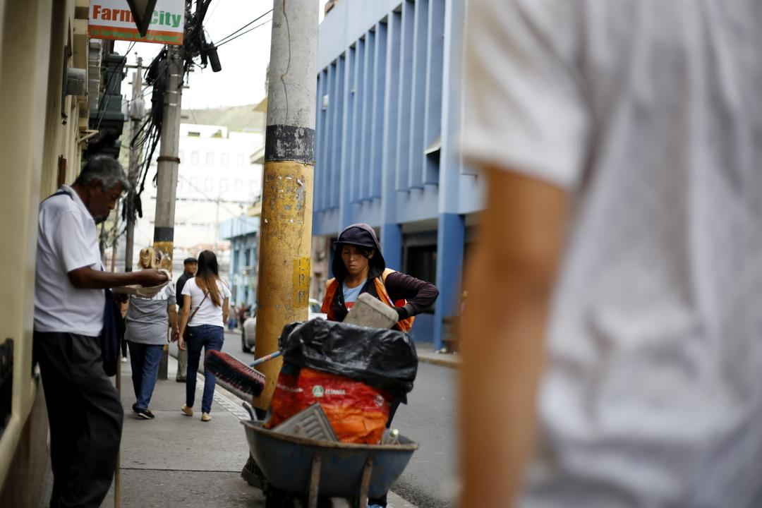 A woman from the municipal cleaning unit works sweeping the Cervantes Avenue in downtown Tegucigalpa. The majority of the city of Tegucigalpa's cleaning workers are poor women who come down from the surrounding neighborhoods of the capital to sweep and pick up garbage from their streets. Photo: Martín Cálix