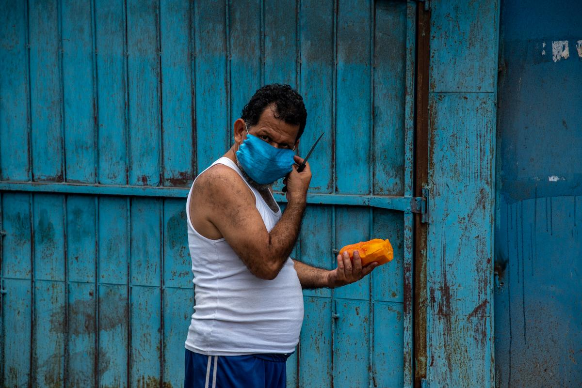 A man wearing a protective mask cuts a papaya in the central marketplace of San Pedro Sula. May, 23rd 2020. Photo: Seth Berry