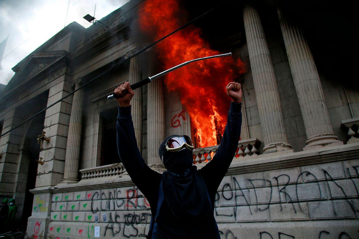 A protester celebrates the burning of Congress. Esteban Biba / EFE /