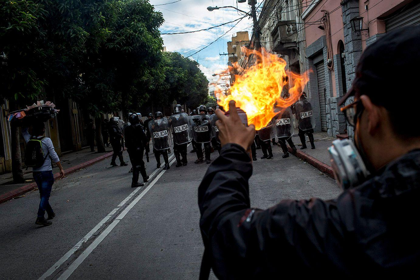 A protester burns gas in front of a riot squad. /