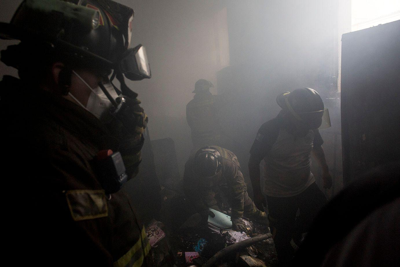 Volunteer firefighters put out the fire inside the Congress, trying to rescue the remains of documents and official records kept in the damaged rooms /