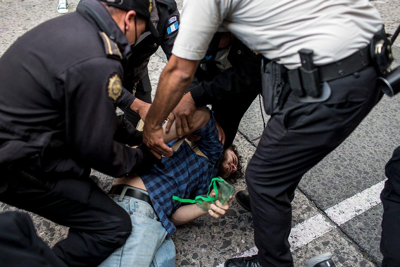 A protester is pinned to the ground by members of the Police. /