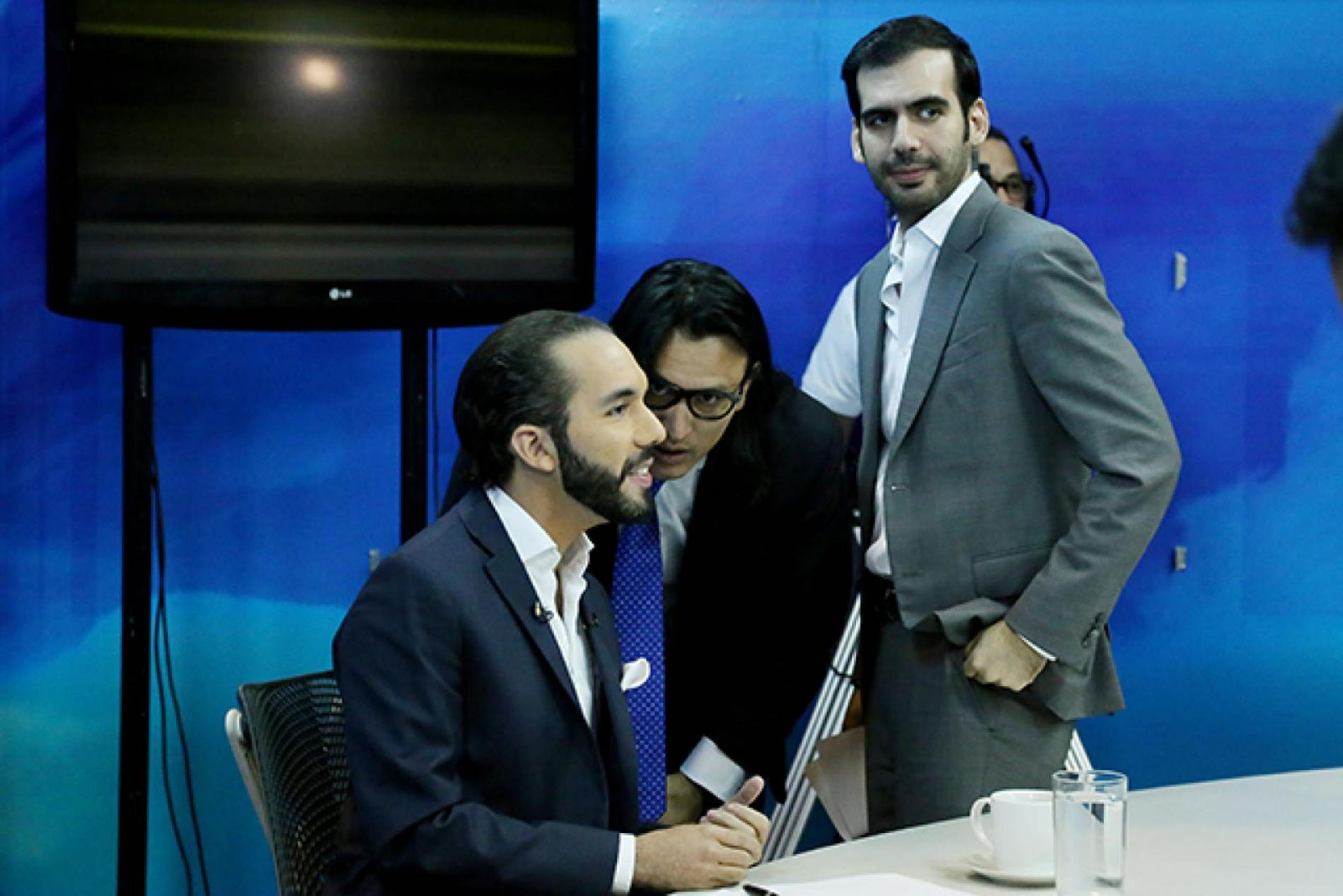 In a January 2015 television debate leading up to the municipal elections, then FMLN mayoral candidate, Nayib Bukele, listens to instructions from Ernesto Sanabria (now his Press Secretary), and his brother, Karim (gray jacket). Photo by Fred Ramos/El Faro archive.
