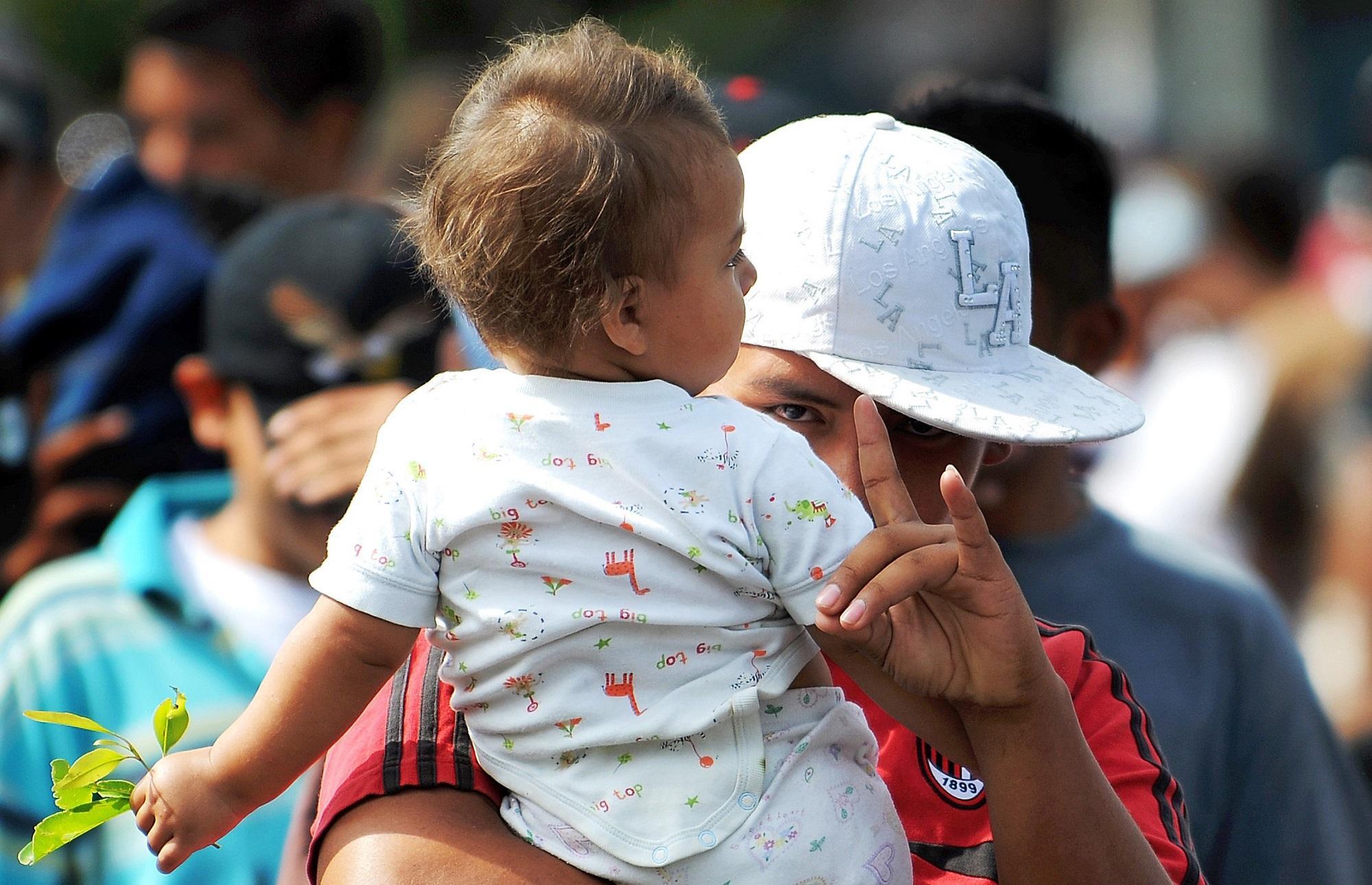 Un joven con un bebé en brazos hace con su mano la garra que simboliza la MS-13. Esta fotografía se tomó el 3 de marzo de 2010, en una marcha de pandilleros y familiares que recorrió las calles de San Salvador.FotoJosé Cabezas (AFP).