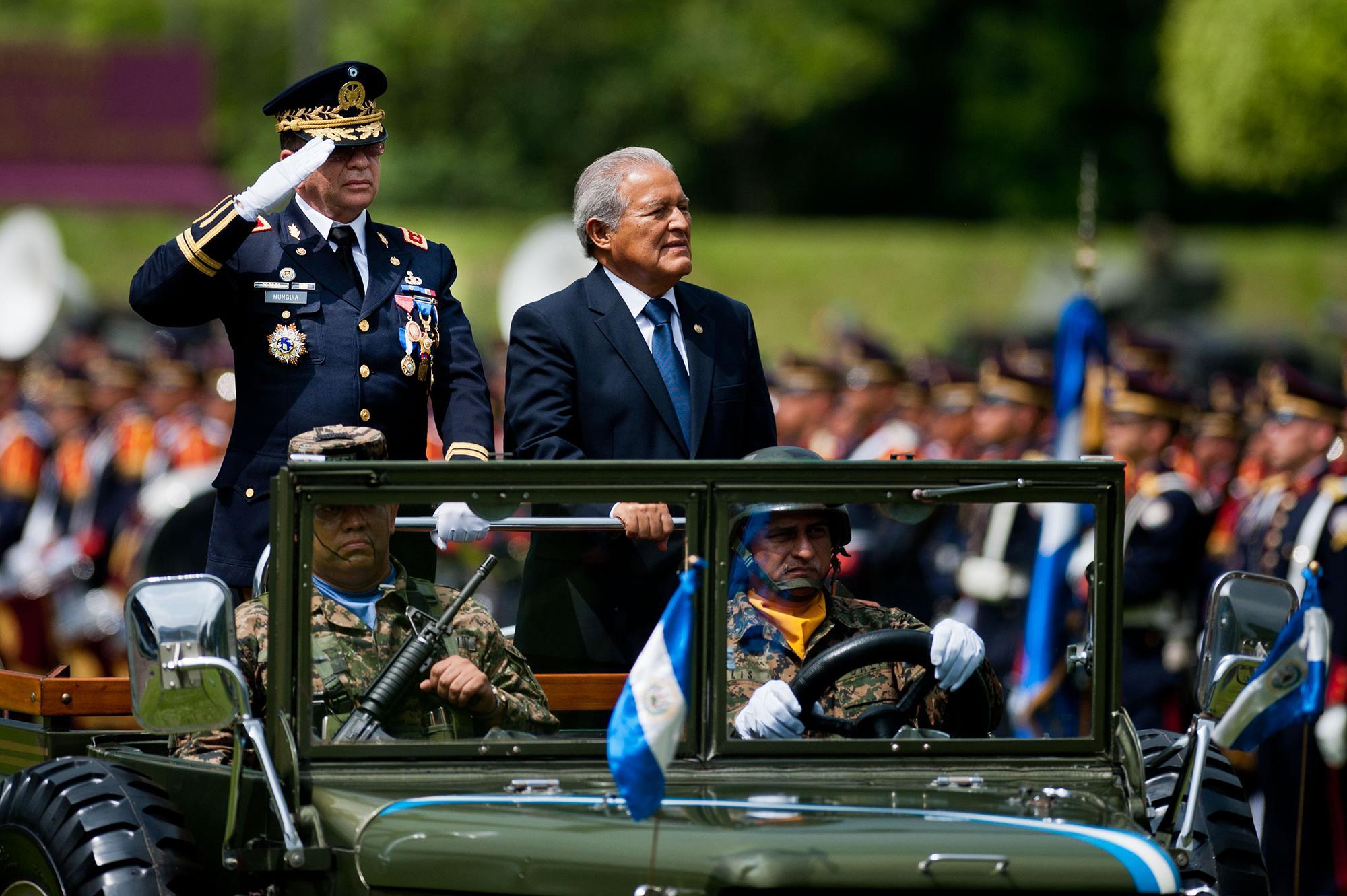 El presidente de El Salvador, Salvador Sánchez Cerén, y el ministro de Defensa, David Munguía Payés, en la ceremonia de revisión de tropas para para presentar al nuevo comandante general de las Fuerzas Armadas, el 5 de junio de 2014. Según los documentos de El Faro, ambos recibían un sobresueldo de $10,000 durante el primer gobierno del FMLN. Foto de AFP: José Cabezas.