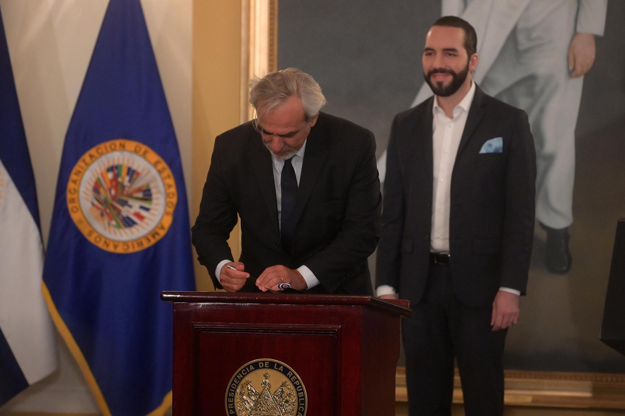 The special envoy of the Organization of American States, Uruguayan Luis Porto (L), signs the letter of understanding next to Salvadoran President Nayib Bukele during a press conference to announce the installation of the International Commission Against Impunity in El Salvador (CICIES) at the presidential palace, in San Salvador, on September 6, 2019. - The government of El Salvador together with the Organization of American States (OAS) announced on Friday the installation of an international commission against impunity that will be responsible for investigating acts of corruption and preventing impunity. (Photo by MARVIN RECINOS / AFP)