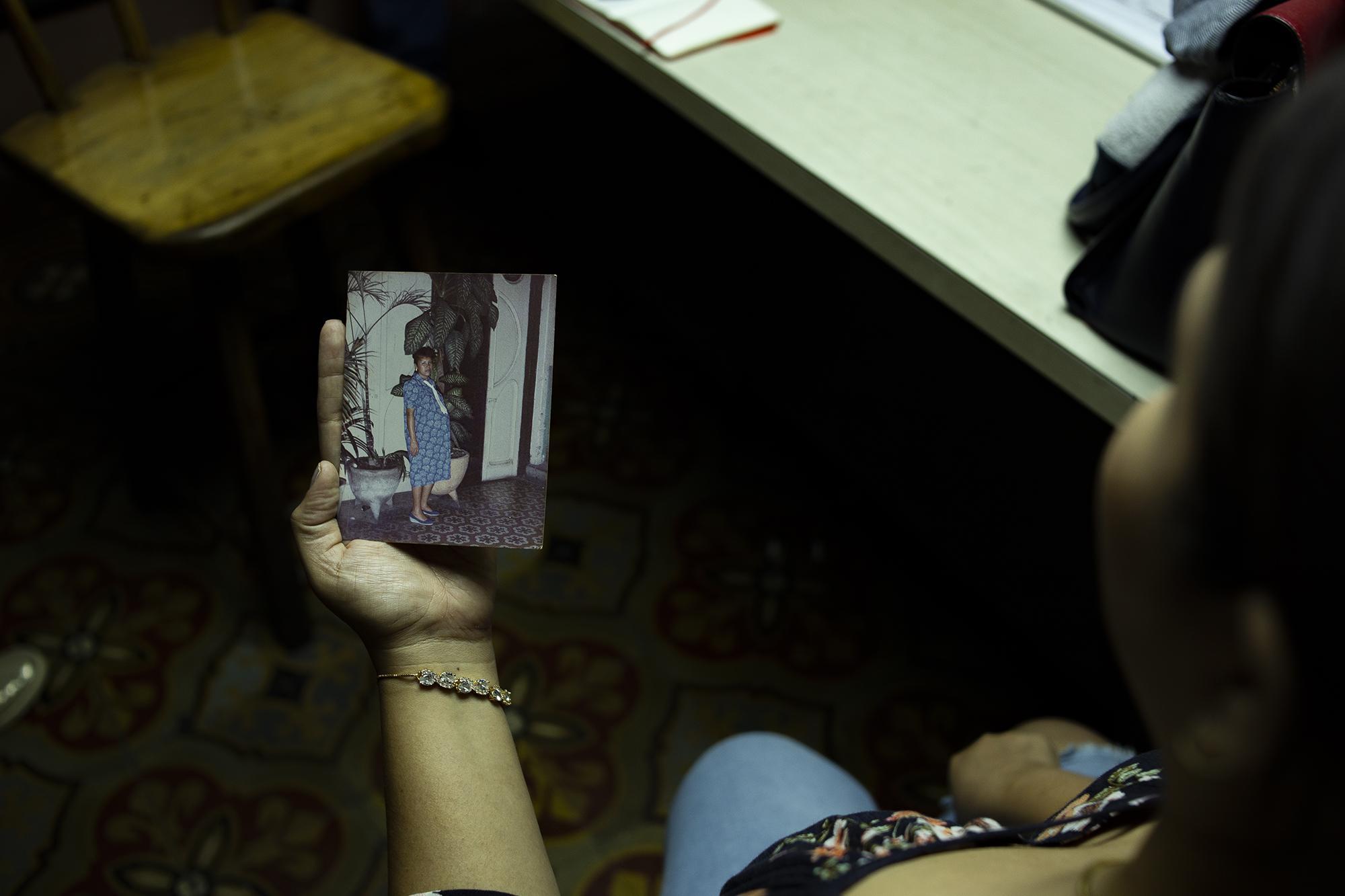 Carla Barrios muestra una fotografía de su madre mientras explica la época en la que ellos vivieron en el club. Nunca ha sentido vergüenza del lugar de trabajo de su papá, pero prefiere no dar la cara por motivos de seguridad.
