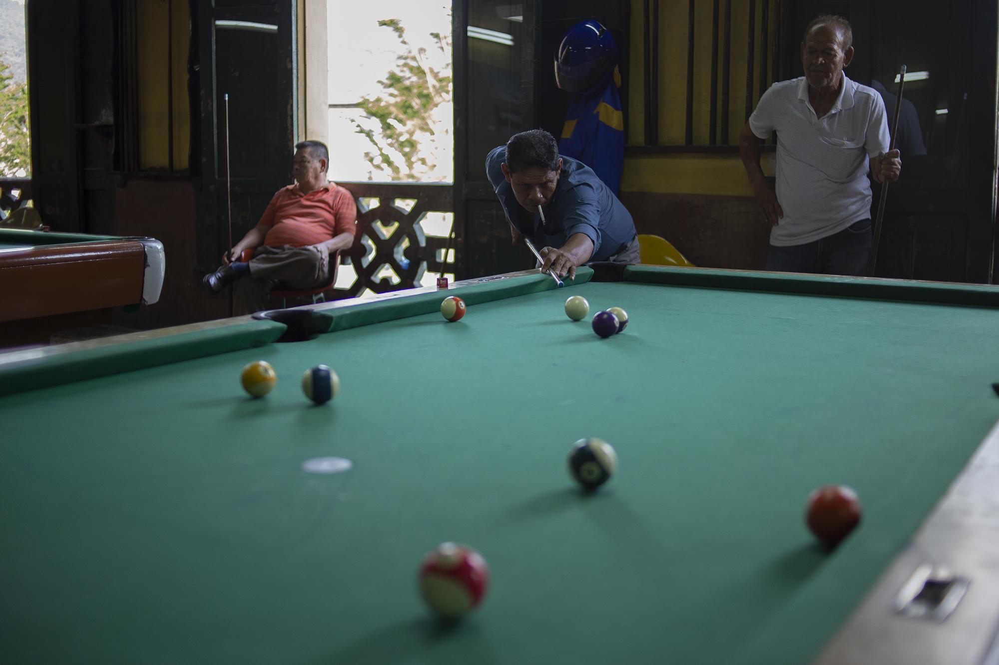 Un grupo de hombres juega una partida de billar en la Dalia. Desde que la nueva ola de visitantes llegan al local, es usual que se quejen por no tener suficiente espacio para manipular el taco.