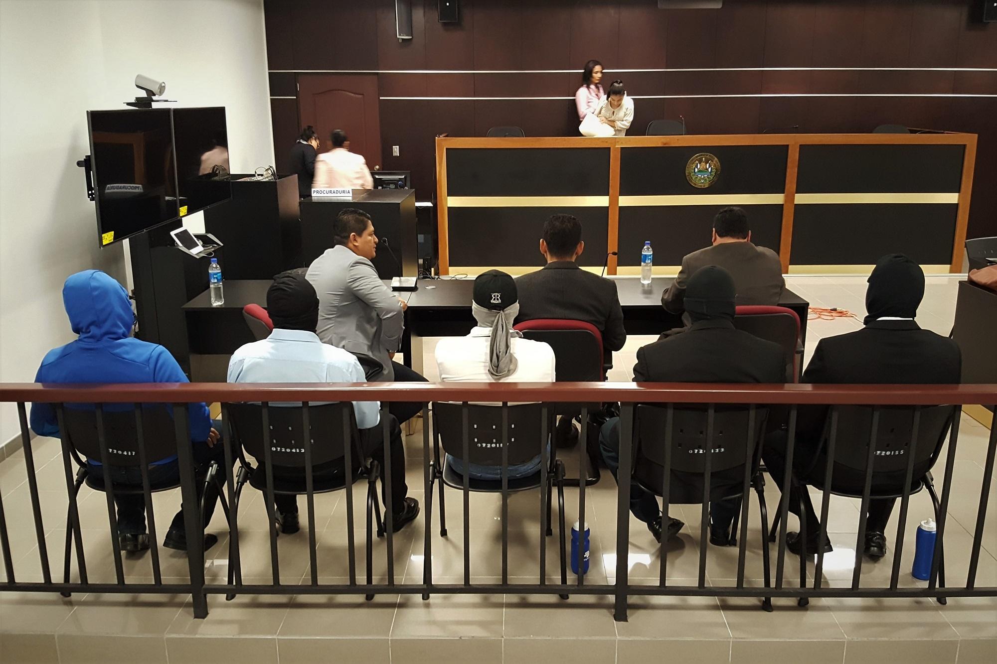Contra la baranda, los cinco agentes del ya extinto Grupo de Reacción Policial (GRP) de la Policía Nacional Civil procesados por el homicidio agravado de Dennis Martínez, trabajador de la finca San Blas, en una imagen tomada durante el juicio celebrado en septiembre de 2017. Foto archivo El Faro.