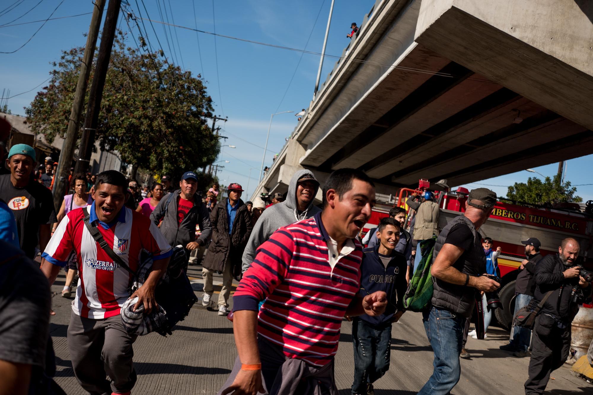 Migrantes centroamericanos corren en dirección al punto fronterizo El Chaparral, el domingo 25 de noviembre. Foto: Fred Ramos
