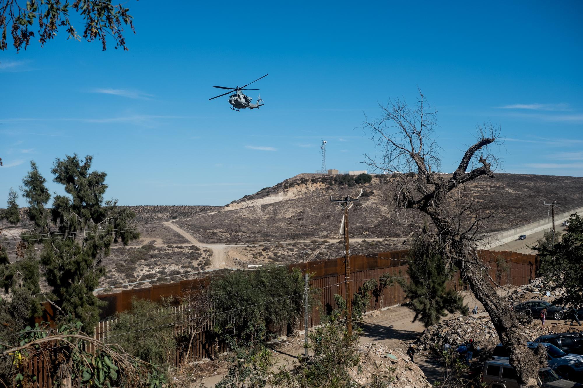 Un helicóptero estadounidense vuela sobre la frontera entre Tijuana y San Diego el domingo 25 de noviembre, mientras cientos de migrantes rondaban el muro. algunas latas de gas lacrimógeno fueron lanzadas desde los helicópteros hacia territorio mexicano. Foto: Fred Ramos