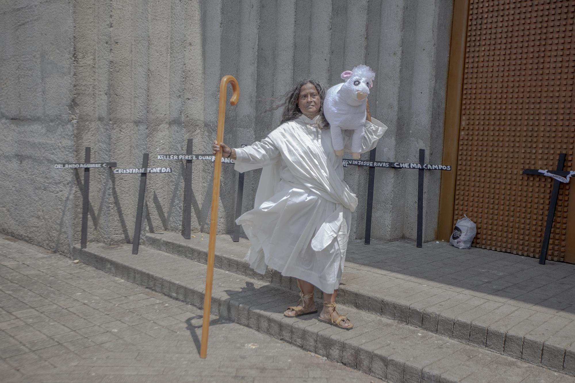 Cruces negras con los nombres de algunas de las víctimas fueron utilizadas como forma de protesta durante el viacrucis afuera de la catedral de Managua el viernes santo. Rosa María, que viste del pastor de la abundancia, posa frente a las cruces.