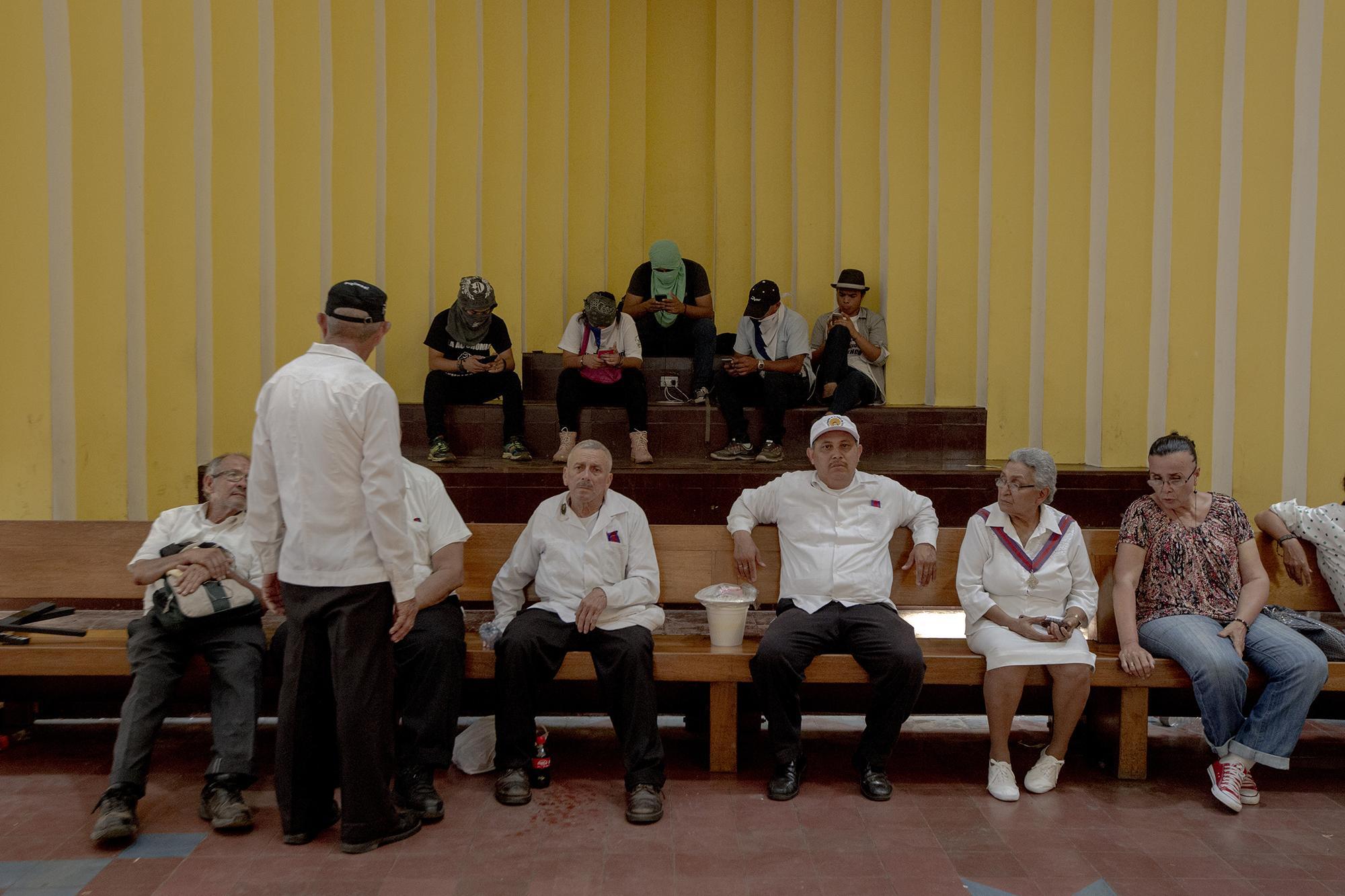 Jóvenes manifestantes (al fondo) y feligreses se resguardan de los ataques de la policía en el interior de la catedral de Managua. Al finalizar el viacrucis del viernes santo algunos de los manifestantes lanzaron piedras a miembros de la policía y estos respondieron con disparos y bombas aturdidoras. La escaramuza, esta vez, no pasó a más.