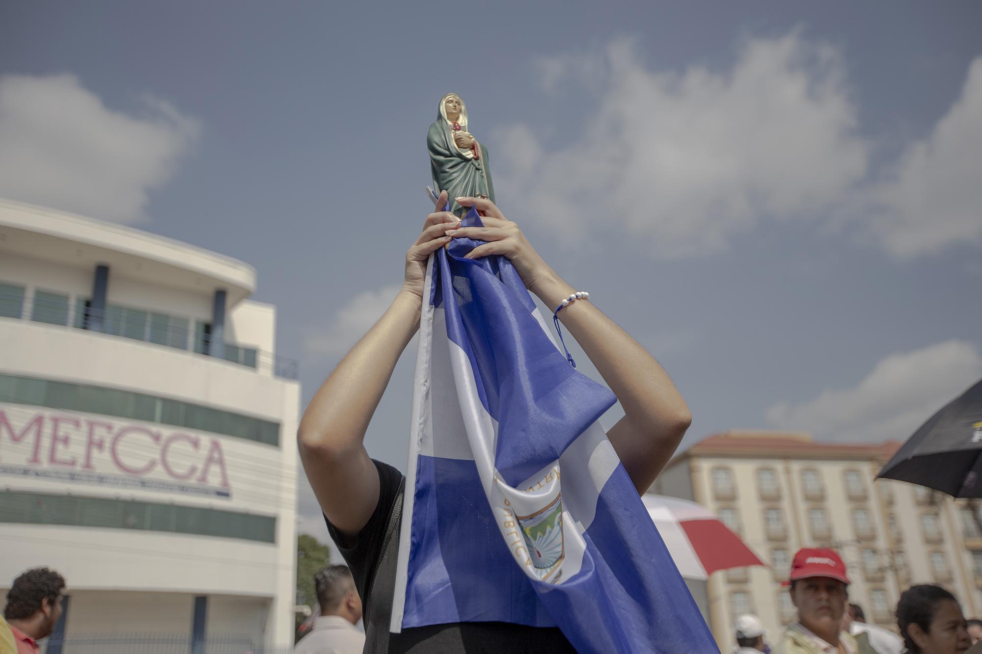 Una mujer nicaragüense carga una imagen de la Virgen Dolorosa con una bandera de Nicaragua durante la procesión del viernes santo en las cercanías de la catedral de Managua. La mujer, quien no brindo su nombre por miedo a sufrir represarías de parte del gobierno o de paramilitares, asegura que llevar la bandera a la procesión es un acto de protesta y de fe por el sufrimiento que ha tenido el país en el último año.