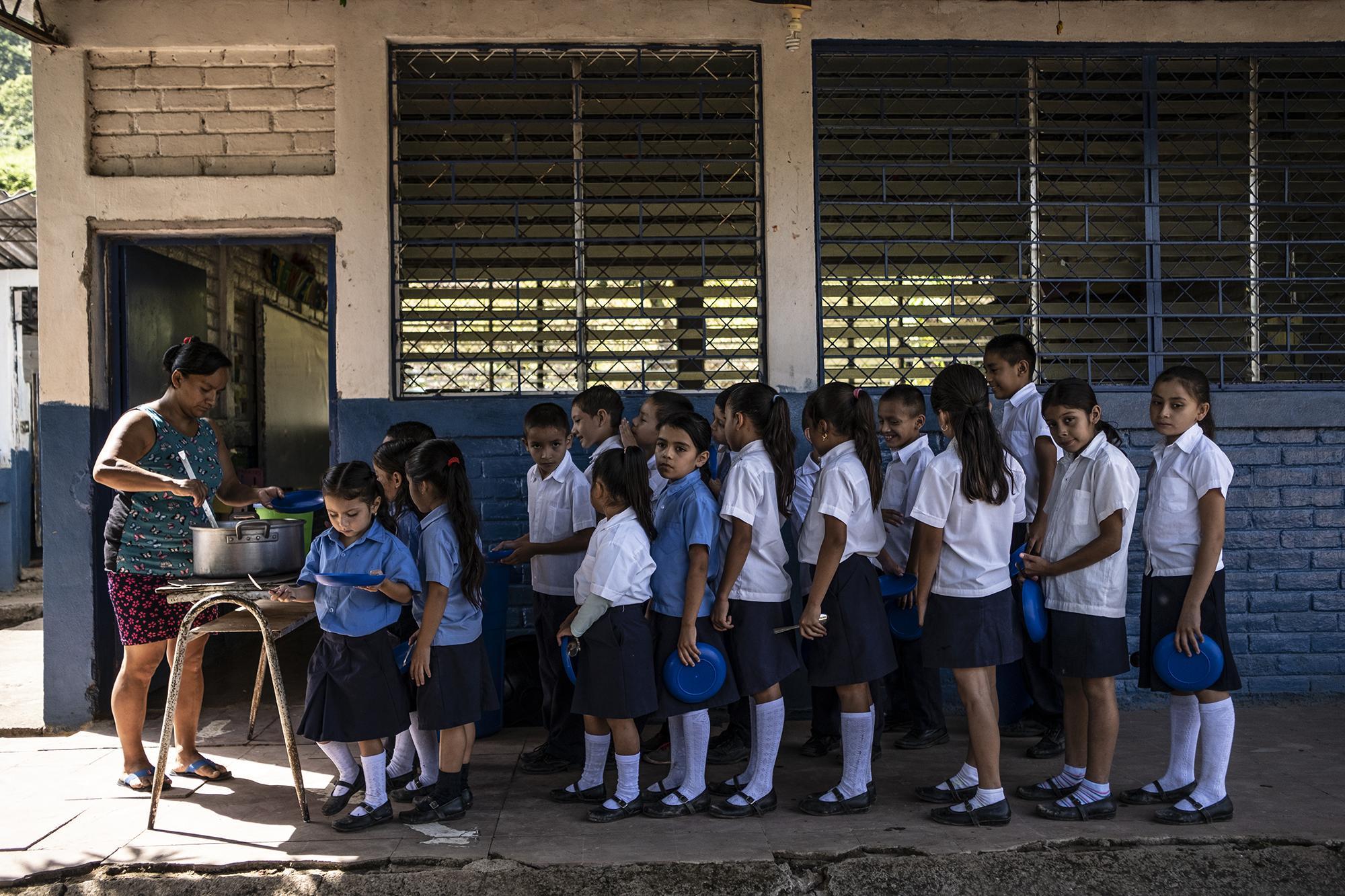 Estudiantes del Centro Escolar Caserío El Tule, en el Cantón El Pinalón, Santa Ana reciben raciones de comida entregada a través del programa de alimentación escolar del Gobierno. Foto, Carlos Barrera.