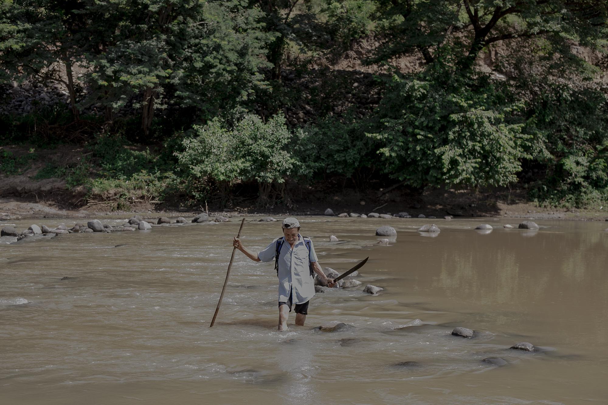 Teofilo Guevara de 55 años, cruza el río Torola para adentrarse al municipio de San Isidro, Morazán. Foto de El Faro   Fred Ramos.