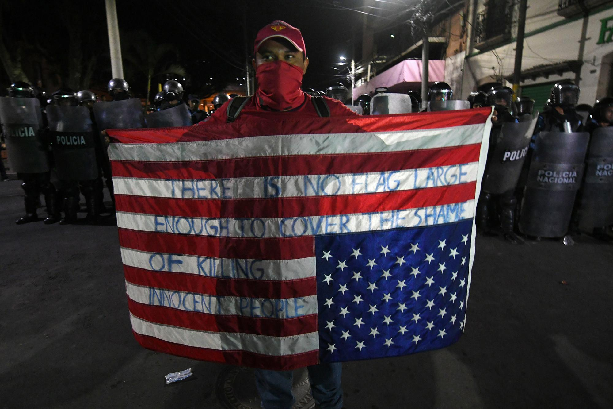 An opposition supporter holds a US flag upside down in front of a line of riot police during a protest demanding the resignation of Honduran President Juan Orlando Hernandez for his alleged links to drug trafficking in the surroundings of the Congress building in Tegucigalpa on October 9, 2019. - Opposition legislators tried to start an impeachment to President Hernandez Tuesday night at the Congress accusing him of drug trafficking, a measure with few possibilities of success in a parliament with a majority of pro-government legislators. A US prosecutor had said on October 2 at the opening of the trial of the Honduran president's brother Tony, that the president himself took fortunes in drug bribes. (Photo by ORLANDO SIERRA / AFP)