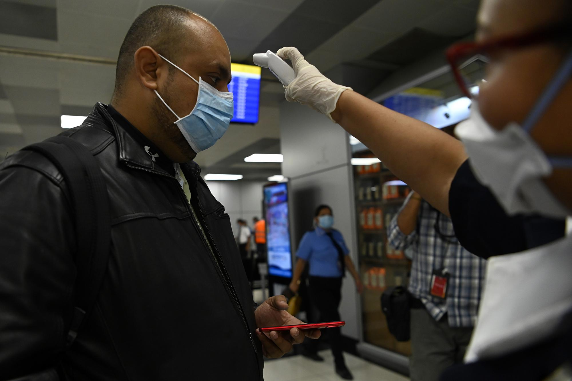 A passenger at El Salvador's international airport gets his temperature checked while wearing a mask to protect against the coronavirus on March 12, 2020. Photo by Marvin Recinos/AFP