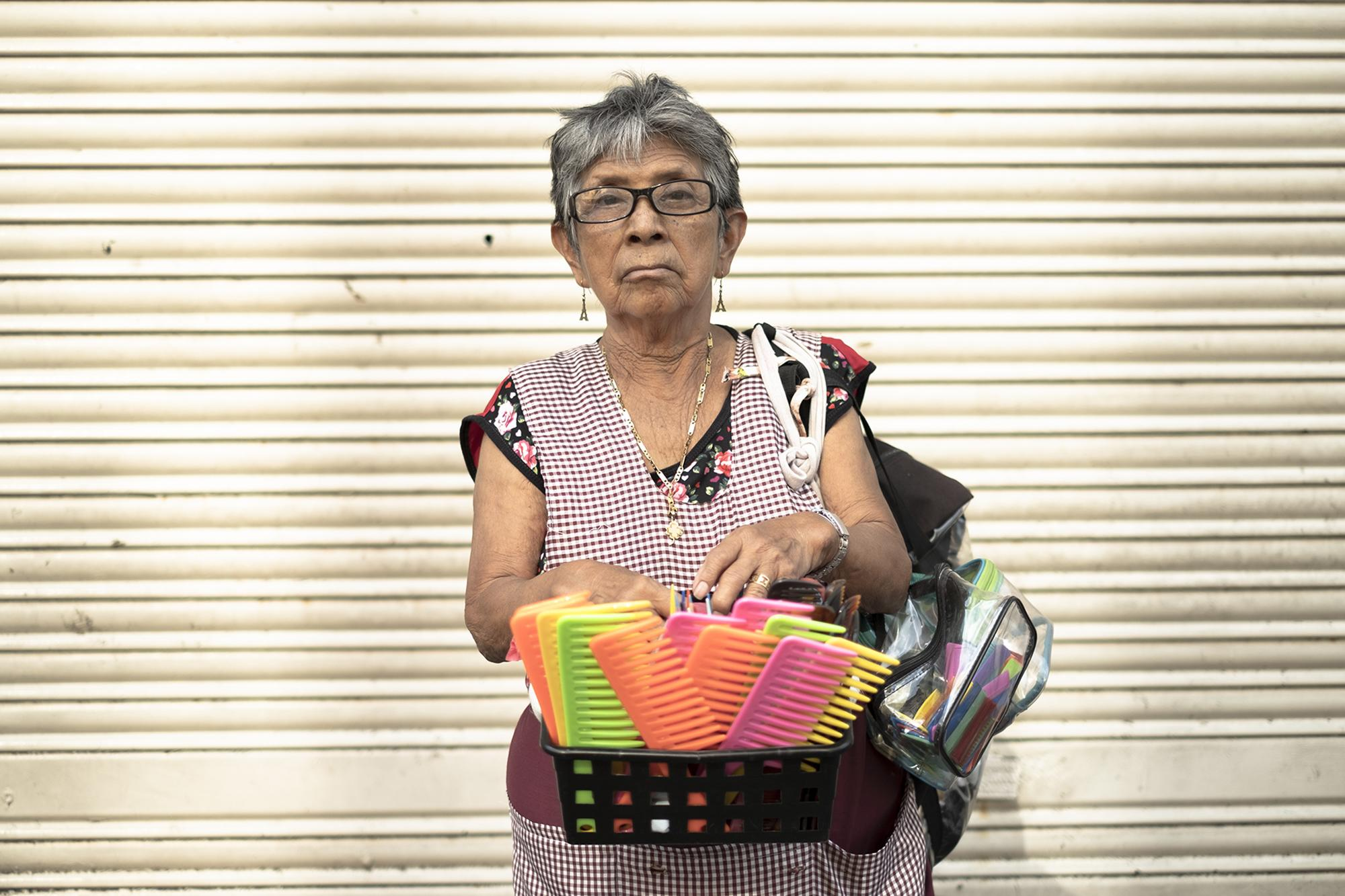 "Esperanza Pérez, 83, lives in Apopa and sells combs in downtown San Salvador. A longtime traveling saleswoman of all kinds of merchandise, she's had to reduce her load with age. ""Maybe the emergency measures will save a few people, especially among those with fixed jobs and a good salary,"" she said. ""But for the old and poor, the only option is to take to the streets to pay for that day's meal."""