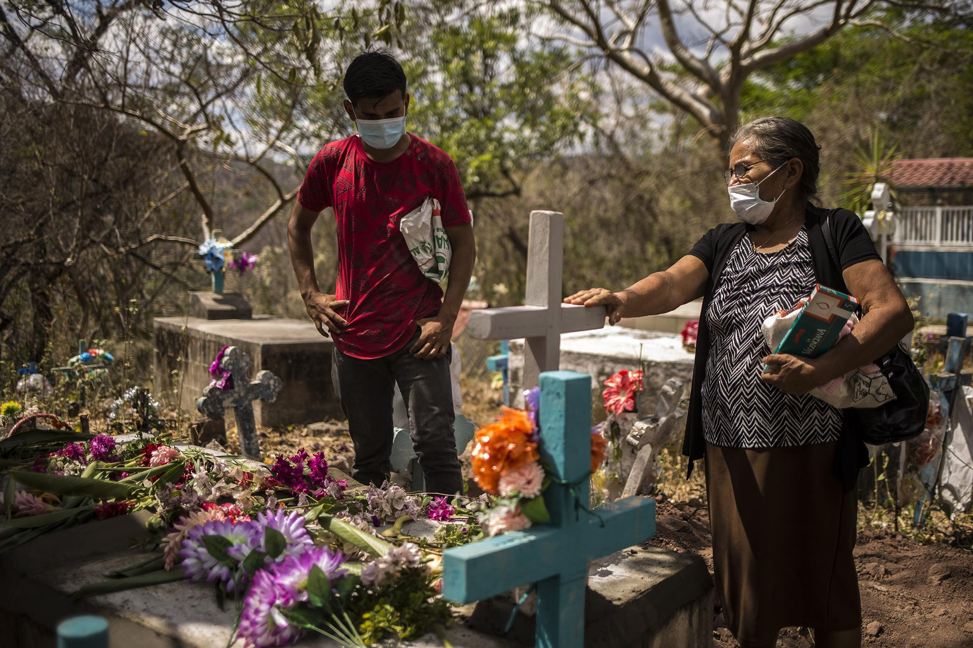 "Rosario López says goodbye to her husband, Ángel Mejía. ""He's in his last house now,"" she said. Municipal Cemetery of Meanguera, Morazán. Photo for El Faro: Víctor Peña."