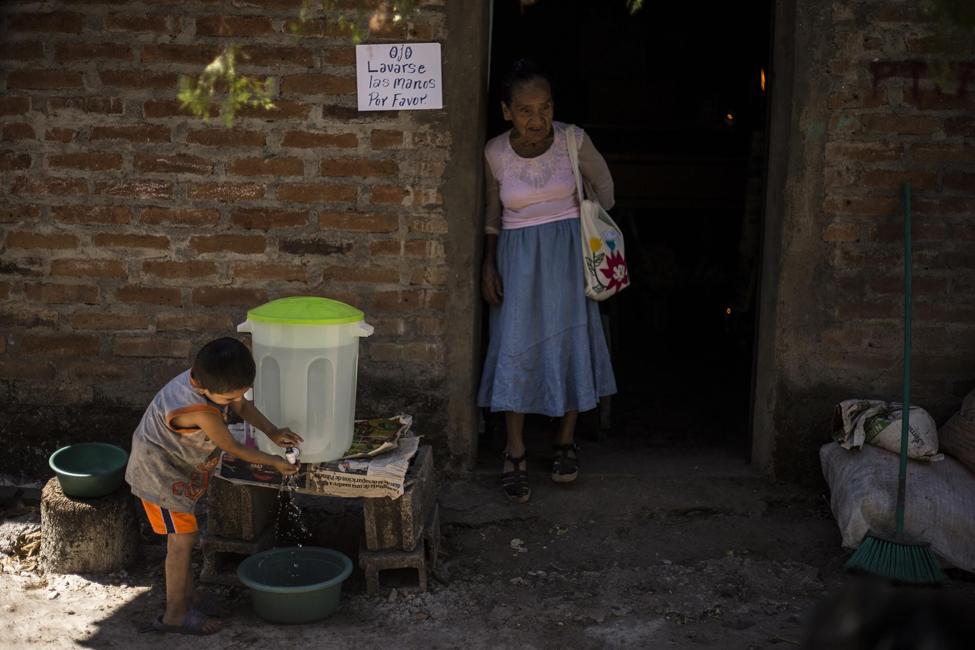 Two-year-old Auner Amaya washes his hands. In the doorway, Don Ángel's 87-year-old sister, María Santos. When news spread of Ángel's death, police arrived at the house to explain hygiene protocols for funerals in response to the COVID-19 emergency. Photo for El Faro: Víctor Peña.