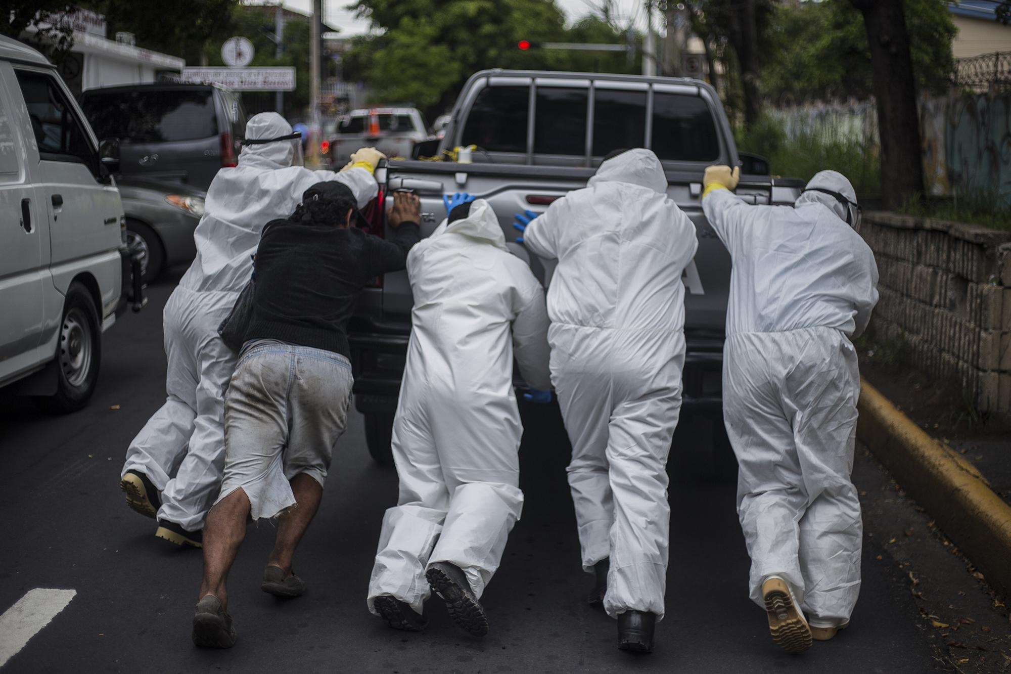 "From 9 am to 3:30 pm every day, cars from funeral homes line up outside the Rosales Hospital in San Salvador to collect the bodies of confirmed or suspected victims of covid-19. ""Once we found 35 victims at the morgue. We sent out 18. The next day I arrived at 6 in the morning and we found another 35 bodies,"" recounts a police officer standing guard outside the hospital. Above, a group of funeral workers tries to jump start a car that caused a bottleneck outside the entrance of the morgue."