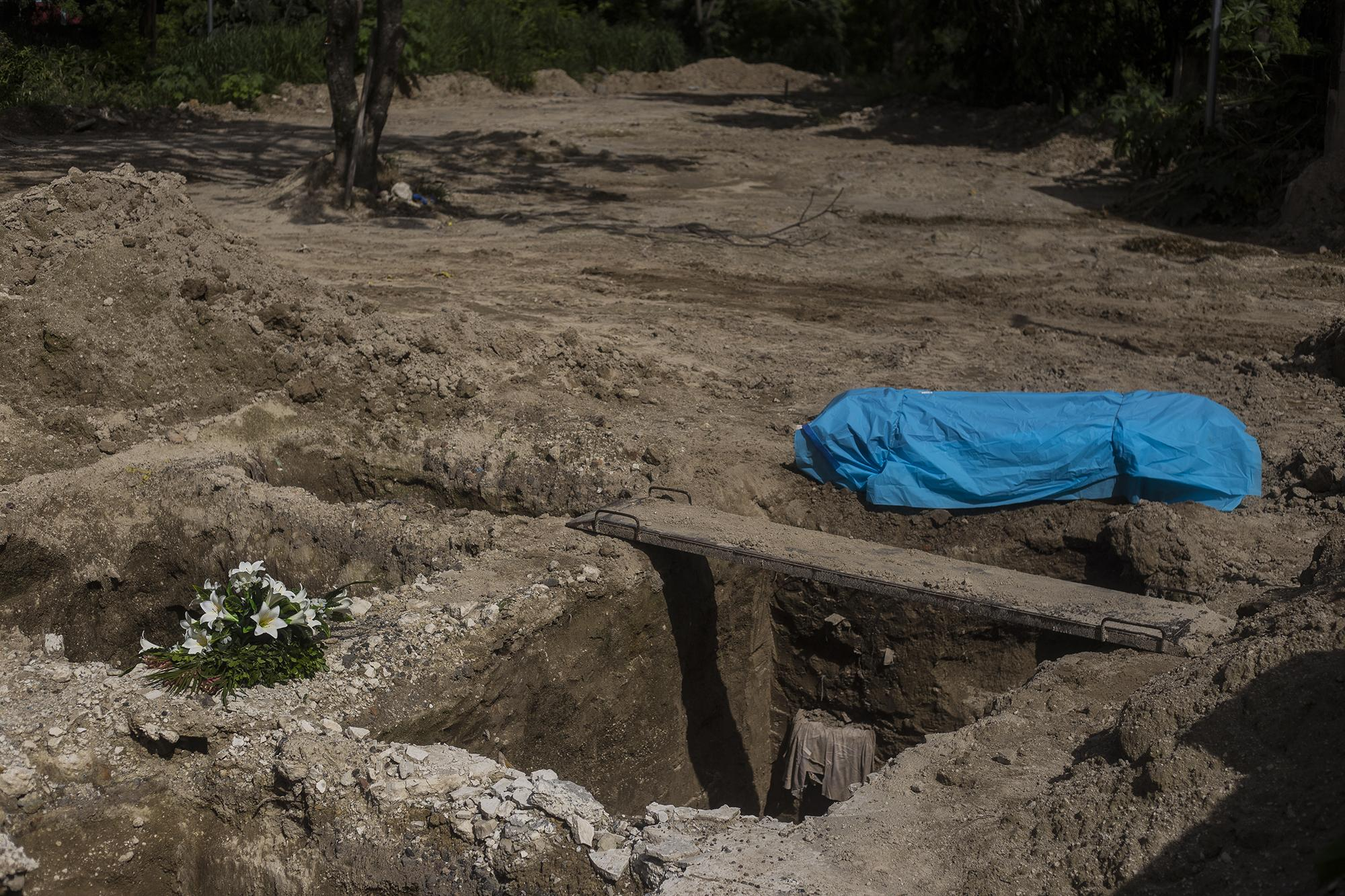 A body awaits its burial under covid-19 protocols in the La Bermeja cemetery in San Salvador. The Ministry of Health has reported a total of 600 burials of suspected or confirmed covid-19 victims since June 19. The hospital network has collapsed, according to patients and medical staff, and some cemeteries in the Metropolitan Area of San Salvador, like Ilopango, are full.