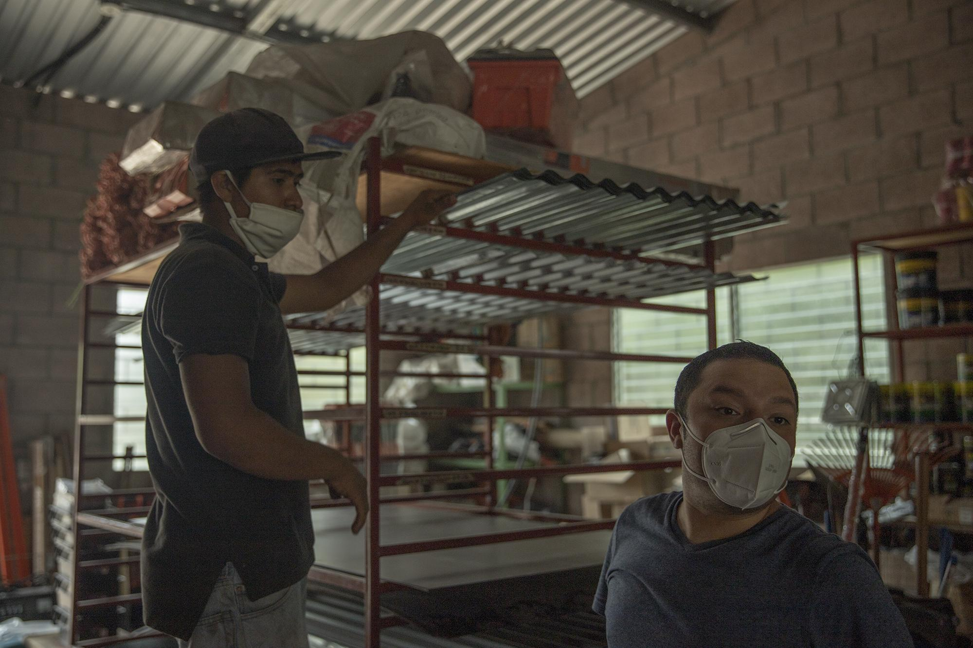 Dino Safie, right, in a hardware store in Verapaz, San Vicente, where he bought sheets of metal and cement blocks to help build a house for a woman in rural Verapaz. Photo: Carlos Barrera/El Faro