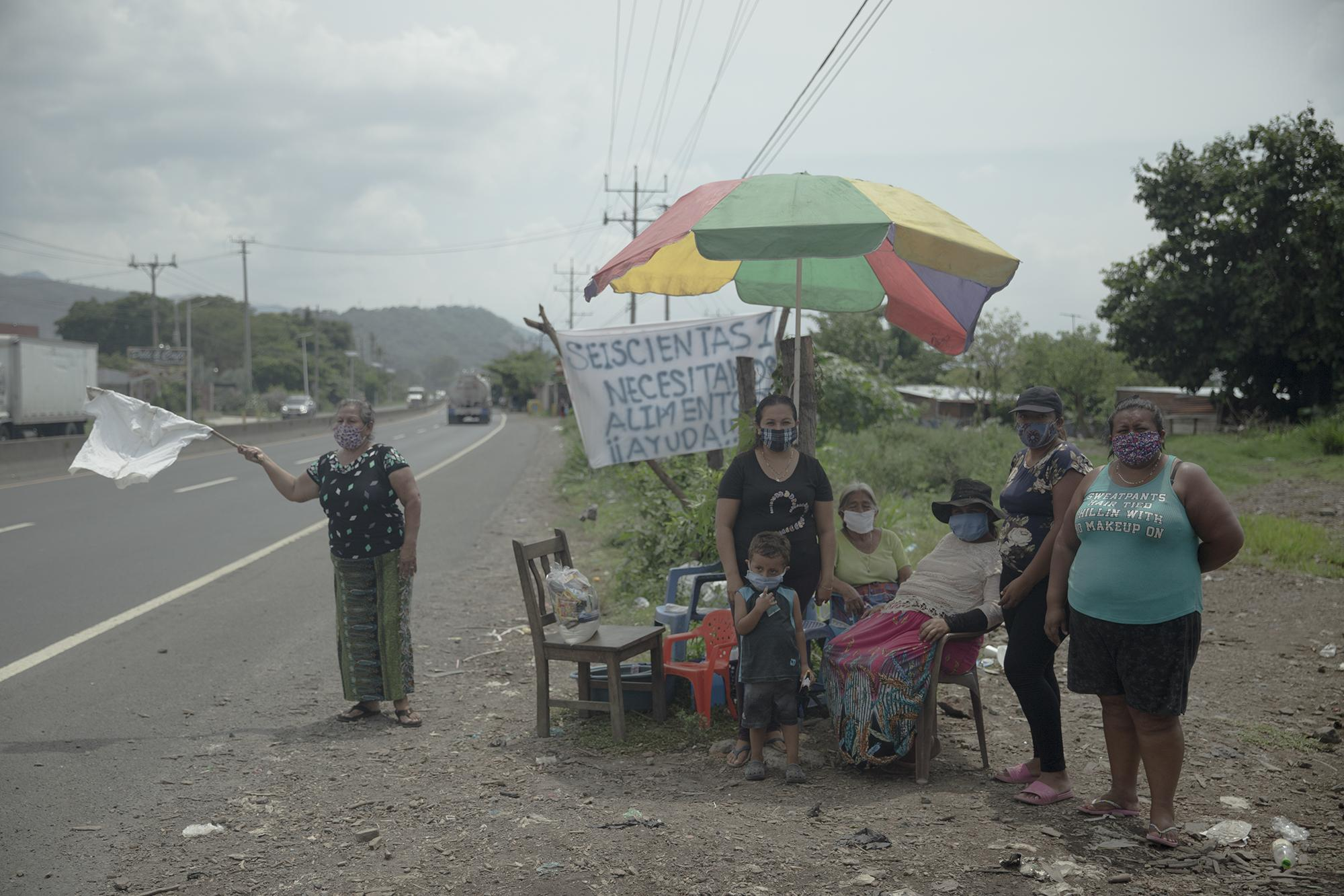 Every day since the start of the quarantine, families in the roadside community Las Seiscientas Uno (The Six-O-One) stand by the highway toward Sonsonate, in the municipality of Colón, La Libertad, asking for food from passersby. Photo: Carlos Barrera/El Faro