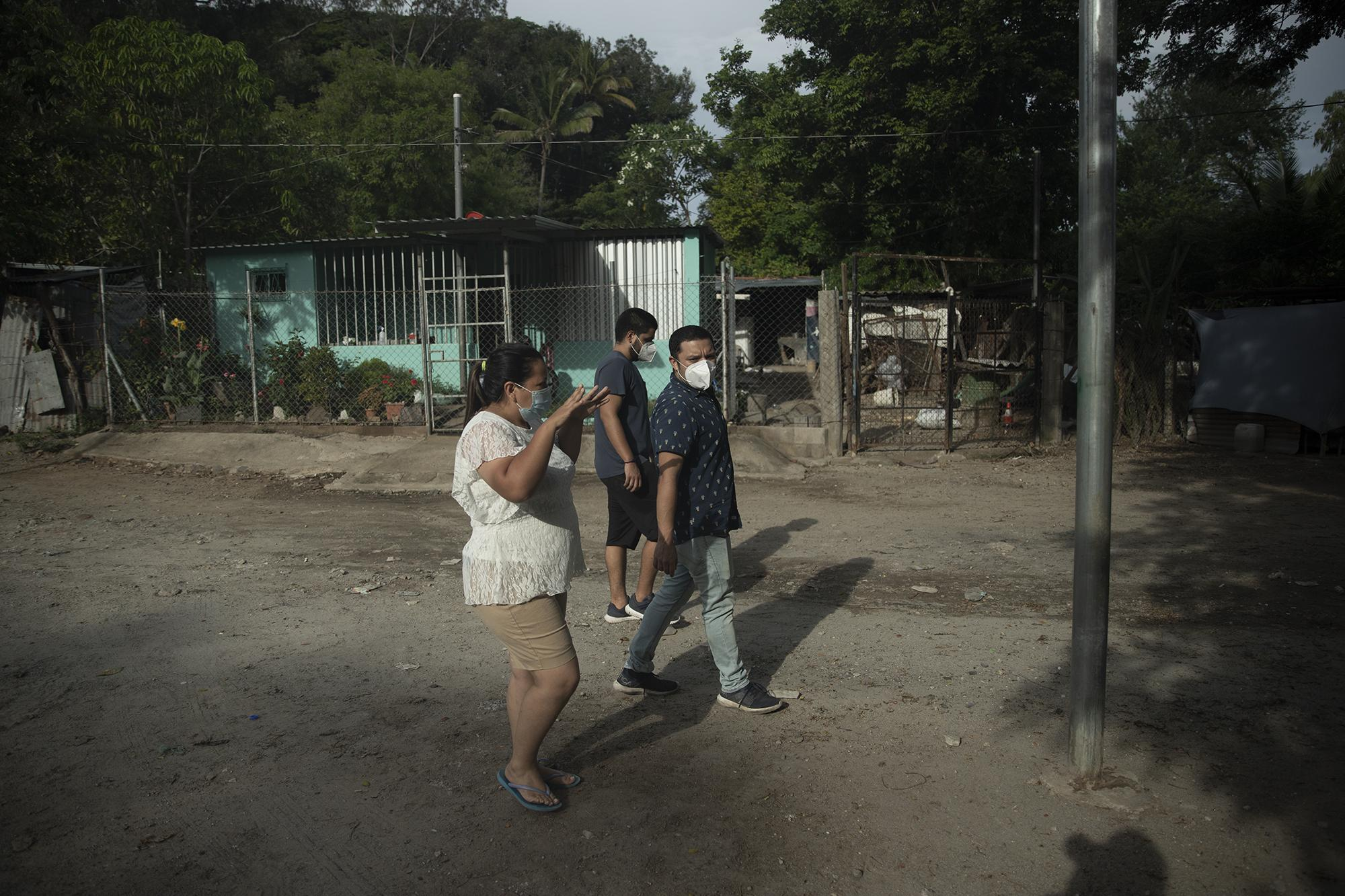 Maribel López walks with Dino Safie and Héctor Silva along the streets of Changallo, Ilopango. As a social worker with the Ilopango mayor's office, she coordinates relief for affected families in Changallo. Photo: Carlos Barrera/El Faro