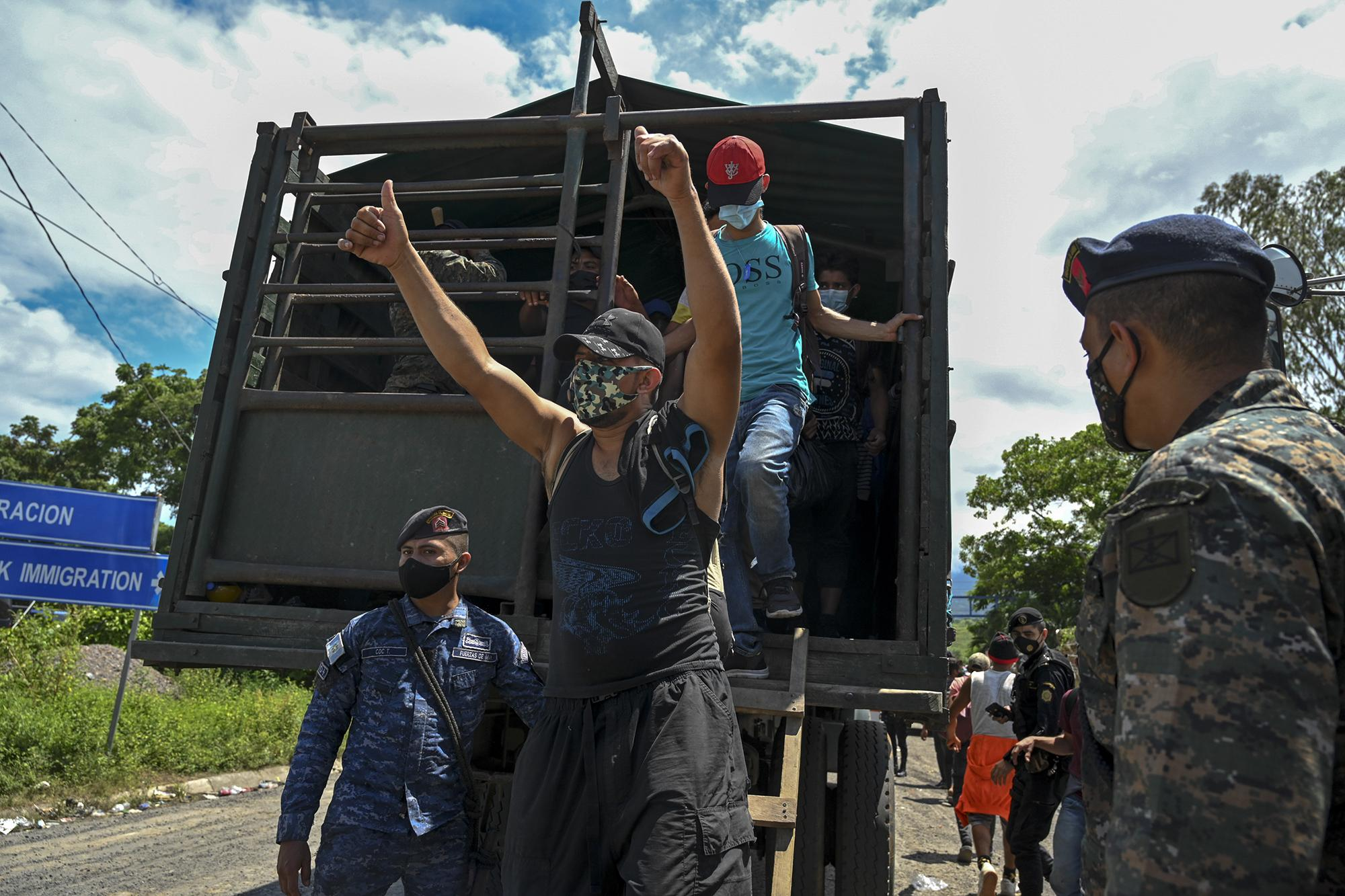 Honduran migrants who were heading in a caravan to the US, get off a Guatemalan army truck after voluntarily agreeing to return to Honduras, in Entre Rios, Guatemala, on October 3, 2020. - Over 2.000 Hondurans requested local authorities to return to their country, according to police data sent to journalists. Guatemalan President Alejandro Giammattei on Thursday had ordered the detention of thousands of Hondurans who entered the country as part of a US-bound migrant caravan. (Photo by Johan ORDONEZ / AFP)