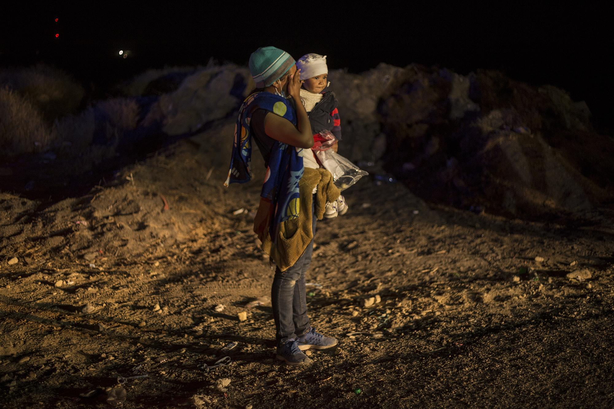 """Una mujer carga a su hijo en brazos frente a la Patrulla Fronteriza. Salió también de entre el monte para entregarse. """"Ya me siento tranquila de estar aquí"""", le dijo a un agente que la recibió. Los patrulleros no facilitaron las condiciones para conversar con los migrantes detenidos."""
