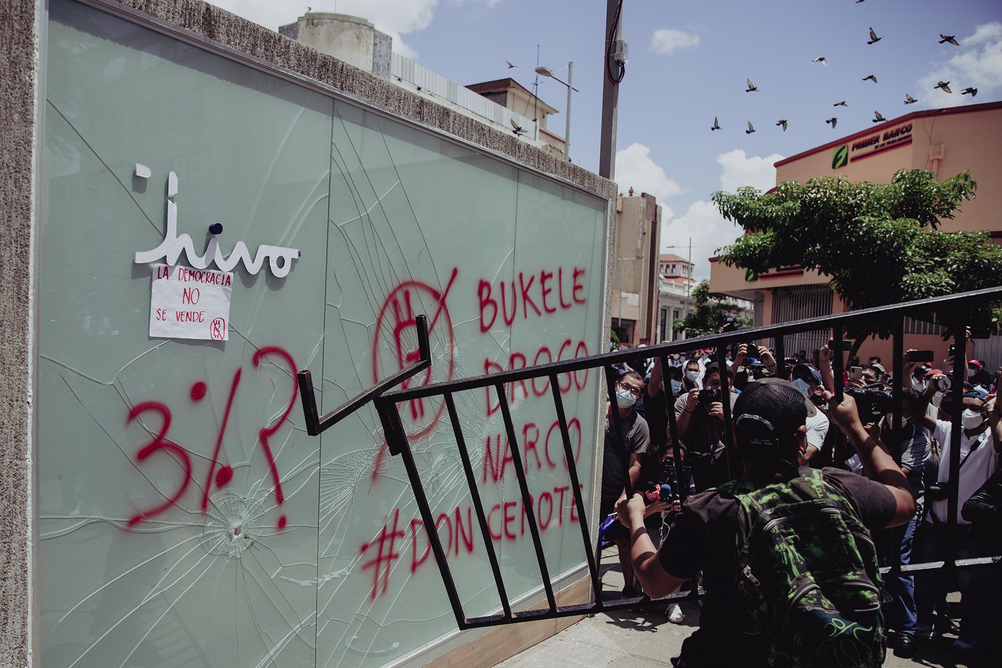 Un reducido grupo de manifestantes intentaba destruir la cabina del cajero de bitcoin ubicado en la Plaza Gerardo Barrios, lo hacían con poco apoyo y alentados por un reducido grupo de personas que los rodeaban. El resto eran curiosos y periodistas que intentaban tener la mejor toma de dicha acción.