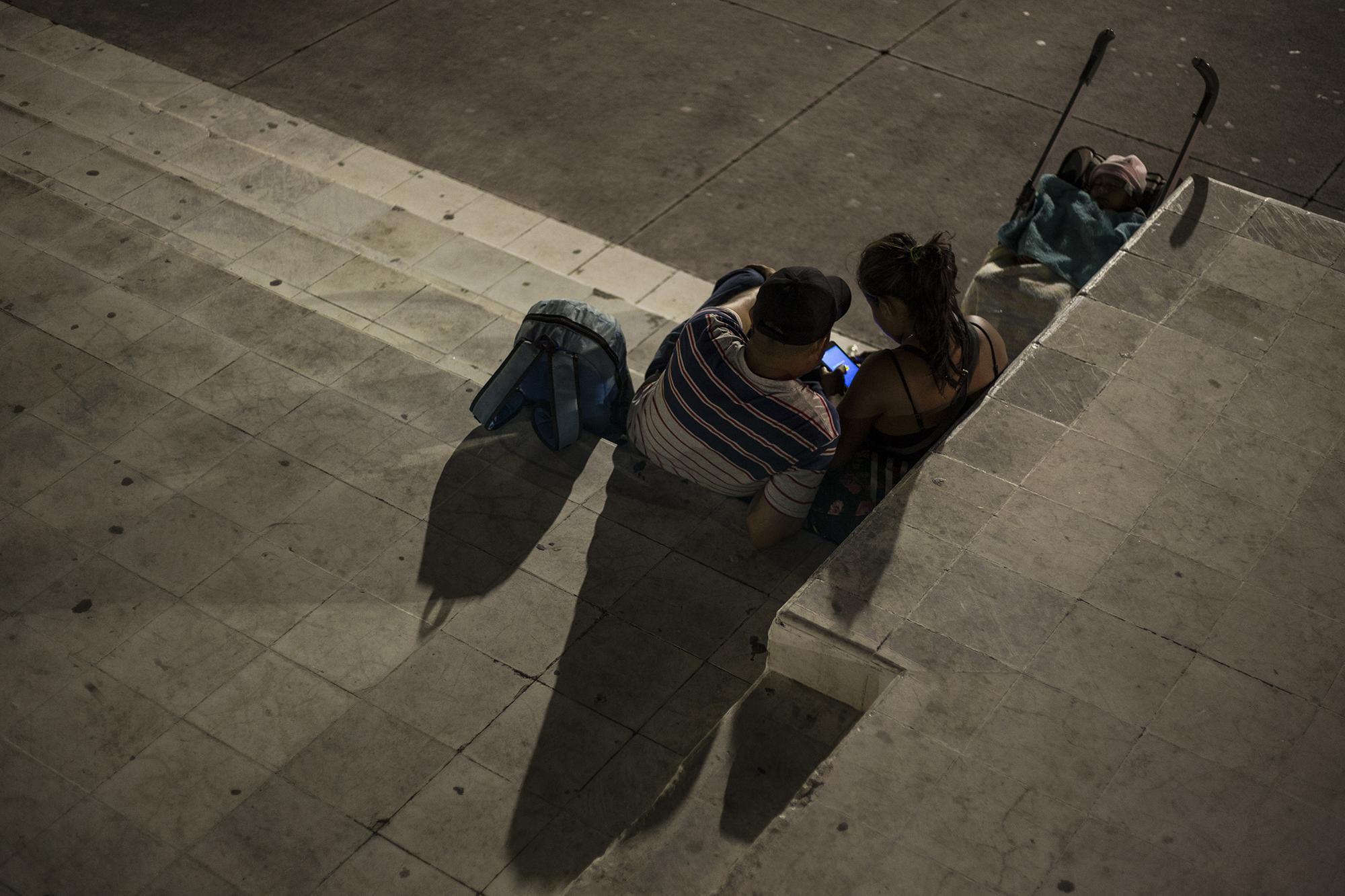 Una pareja originaria del municipio de Tonacatepeque, departamento de San Salvador, espera la salida de la nueva caravana. Al igual que Kevin, la pareja huye de amenazas de pandillas en su municipio. Foto: Víctor Peña.