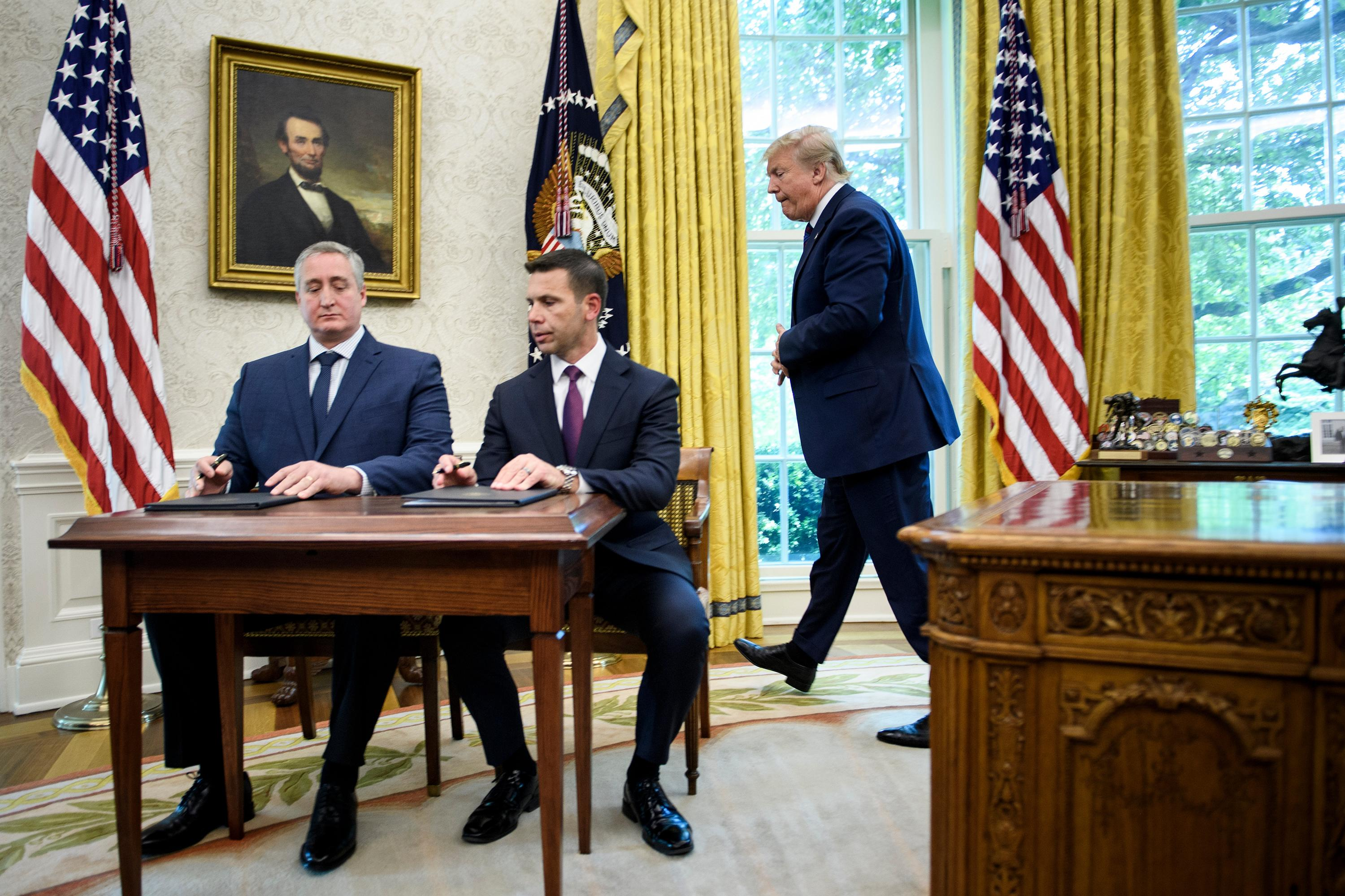US President Donald Trump walks to watch as Guatemala's Interior Minister Enrique Degenhart (L) and Acting US Secretary of Homeland Security Kevin K. McAleenan (C) sign a safe-third agreement, regarding people seeking asylum while passing through Guatemala, in the Oval Office of the White House on July 26, 2019 in Washington, DC. (Photo by Brendan Smialowski / AFP)