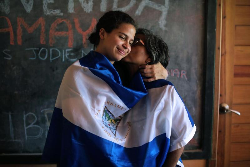 Student activist Amaya Coppens (left) is kissed by her mother while wrapped in the Nicaraguan flag. Coppens was jailed for protesting Ortega's regime. She said prisoners were tortured and mistreated. Photo by Inti Ocon/AFP.