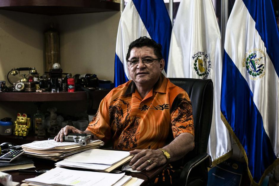 Catalino Miranda, with a gun on his desk in San Salvador, owns a fleet of buses and refuses to yield to extortion demands. Fred Ramos/El Faro for The New York Times